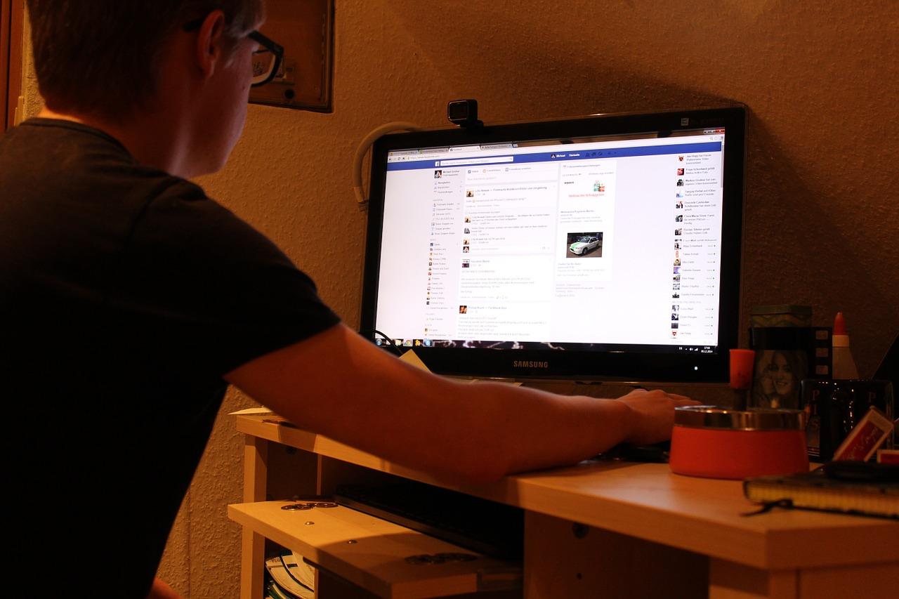 man vid dator på facebook