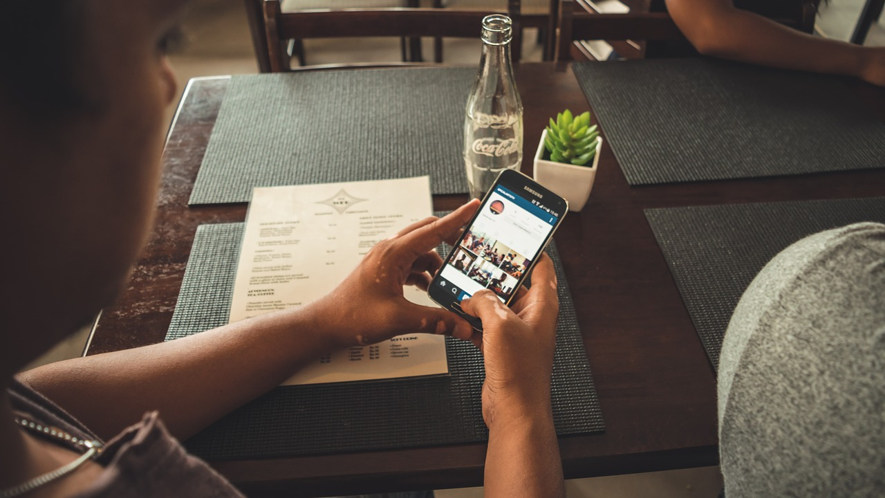 man använder instagram på restaurang